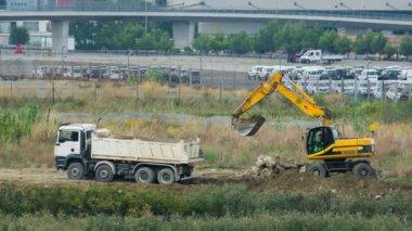 грузовик вождение назад получить загружен с лопатой экскаватор в полной почвы — Стоковое видео