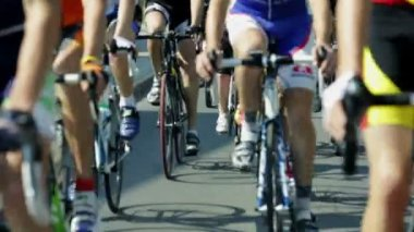 Shallow focus shot of cyclists lower bodies while riding bikes in cycling race — Stock Video