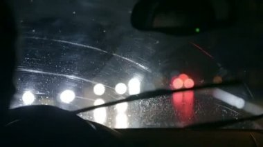 Car wipers are removing rain at slow nightdrive throught the city — Stock Video