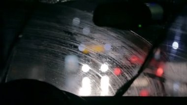 Car wipers are wiping windscreen in a city nightdrive — Stock Video
