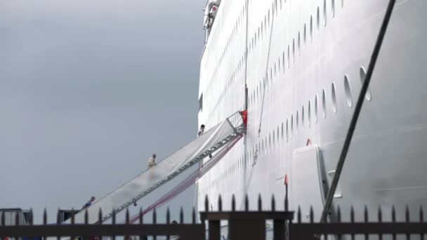 Tiro de personas subiendo las escaleras al tablero blanco crucero hizo detrás de la cerca — Vídeo de stock