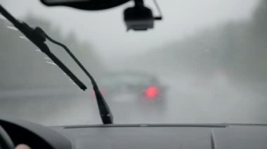 Car wipers removing rain from windshield while driving right after some car — Stock Video