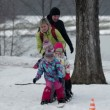 Family trying to walk on large skis when kid falls — Stock Video #38474109