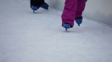 Blue kiddie skates staggering on ice rink — Stock Video