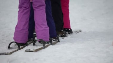Legs of kids trying to synchronize their walking on wooden skis — Stock Video