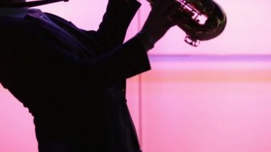 Man figure enjoying playing sax at night with purple background — Stock Video