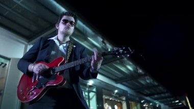 Man with sunglases playing red guitar in slow motion — Stock Video