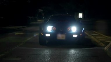 Corvette is slowly approaching the camera with the headlights light up — Stock Video