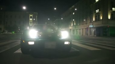 Car is slowly driving through the city at night — Stockvideo