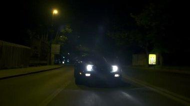 Car driving towards the camera at night city drive — Stock Video