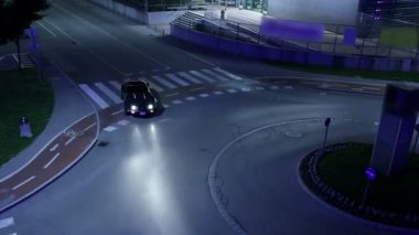 Corvette driving through roundabout shot from the top view at night — Stock Video