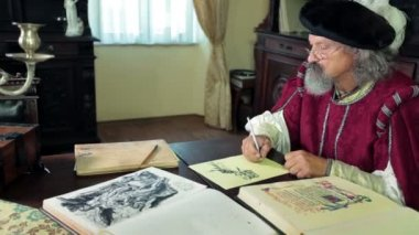 An old medieval scholar checks some documents — Vídeo Stock