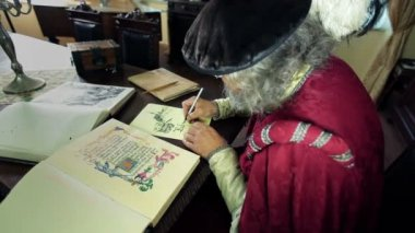 Writer in medieval clothes writing in caligraphy — Stock Video
