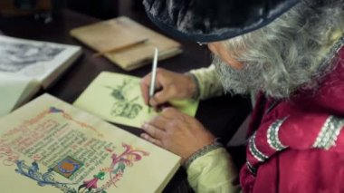 An old medieval scholar writing in calligraphic writing — Vídeo Stock