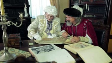 Mayor and scholar in medieval clothes talking about an old open map — Stock Video