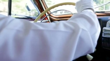 Man in white shirt steering a wheel in vintage car — Stock Video