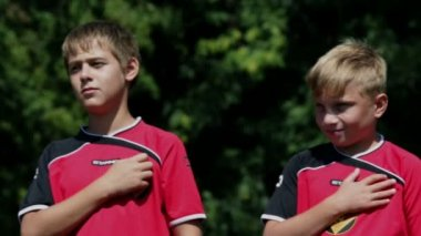 Young footballers listening to the national anthem on in the middle of the field — Stock Video