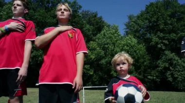 Kids listening to the national anthem in football dress — Stock Video