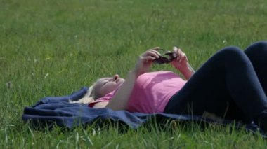 Woman takes off the sunglasses and rests on the grass under the sun — Stock Video