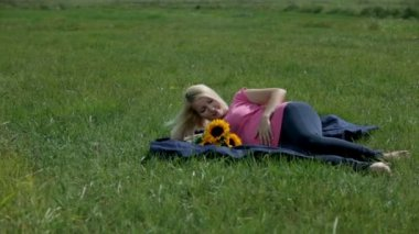 Woman stroking her stomach while resting on the blanket with sunflowers bouquet — Stock Video