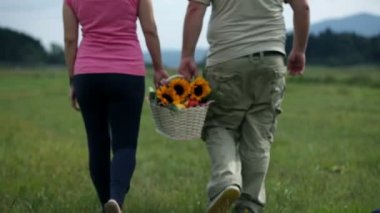 Couple holds white basket with sunflowers and walks away from the camera — Stock Video
