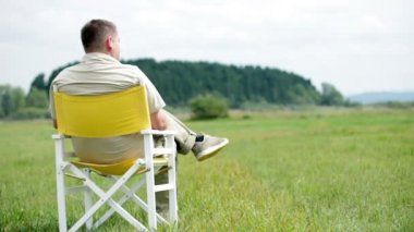 Man sits on a white picnic chair and observes the nature aroud him — Stock Video