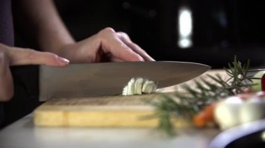 Cutting the onion into pieces on a wooden plate — Stock Video