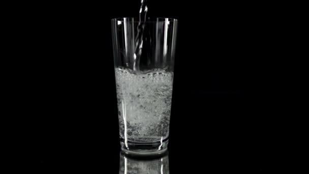 Vertiendo agua en ya medio vaso lleno de agua de riego — Vídeo de stock