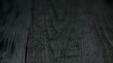 Sliced orange falls onto dark wooden-like surface and disintegrates — Stock Video