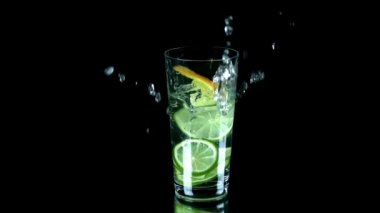 Peces of citrus fall into water on black background and spill some water — Stock Video