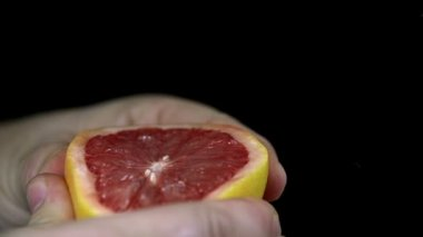 Squeezing a grapefruit which spurts its juices in slow motion — Stock Video