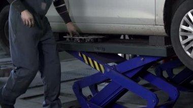 Auto mechanik dźwigów samochodowych i usuwa felgi — Wideo stockowe