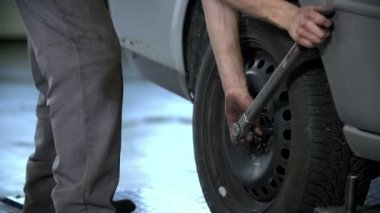 Mechanic tightenes the screws on the tires at the back of the car — Stock Video
