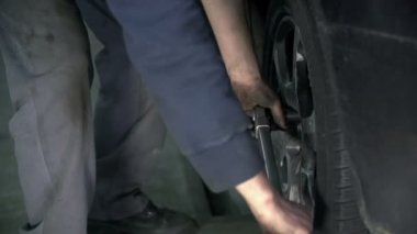 Close shot of man fastening the screws back to the rim — Stock Video