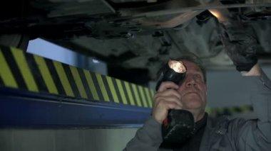 Mechanic checks the bottom of the car — Stock Video