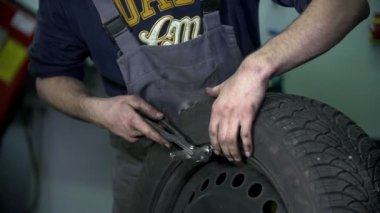 Vulcaniser hammers a metal piece into the tire — Stock Video