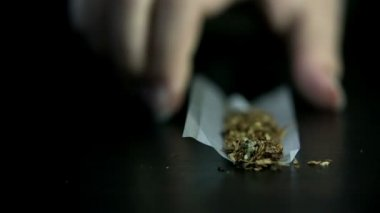 Picking up rolling paper with tobacco and marihuana — Stock Video