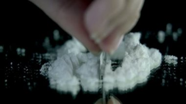 Preparing cocaine for sniffing on the black backgrond in slow motion — Stock Video