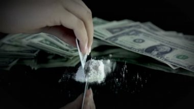 Female making some cocaine lines with credit card with money bills in the back — Stock Video