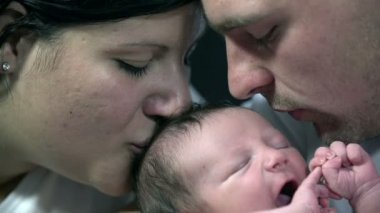 Both parents kiss baby boy's head at the same time — Stock Video