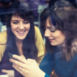 Two girls smiling and using smart phone in a cafe — Stock Photo