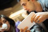 Man och kvinna med tabletten i ett café — Stockfoto