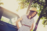 Retro style young woman standing next to the car — Stock Photo