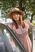 Retro style young woman standing next to car — Stock Photo