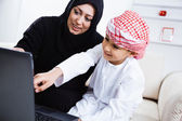 Arabic mother and son using laptop — Stock Photo