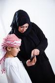 阿拉伯妇女和使用智能手机的儿子 — 图库照片