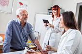 Doctor Checking Blood Pressure to Man — Stock Photo