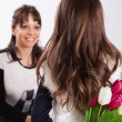 Girl giving her mother flowers — Stock Photo #50507631