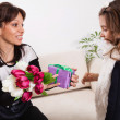 Girl giving her mother flowers — Stock Photo #50507641