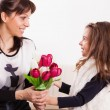 Girl giving her mother flowers — Stock Photo #50507657